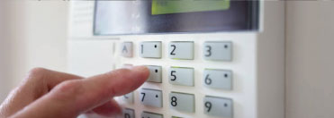 Hand entering code on security keypad